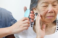 Ηλικιωμένη γυναίκα που κτενίζει την τρίχα από το caregiver στοκ εικόνες