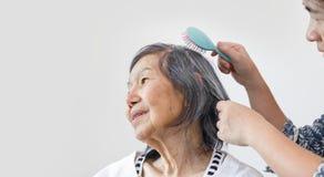 Ηλικιωμένη γυναίκα που κτενίζει την τρίχα από το caregiver στοκ φωτογραφία