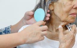 Ηλικιωμένη γυναίκα που κτενίζει την τρίχα από το caregiver στοκ εικόνα με δικαίωμα ελεύθερης χρήσης