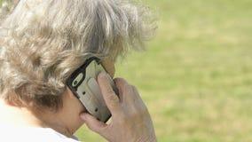 Ηλικιωμένη γυναίκα που μιλά χρησιμοποιώντας ένα έξυπνο τηλέφωνο υπαίθρια απόθεμα βίντεο