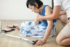 Ηλικιωμένη γυναίκα που πέφτει κάτω στο σπίτι, επίθεση δαπέδων τζακιού στοκ εικόνες