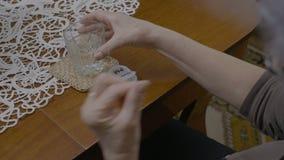 Ηλικιωμένη γυναίκα που παίρνει το φάρμακο πρωινού της από έναν αρμόδιο για το σχεδιασμό χρονικών χαπιών και ένα πόσιμο νερό - απόθεμα βίντεο