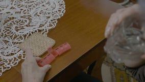 Ηλικιωμένη γυναίκα που παίρνει το φάρμακό της από έναν καθημερινό αρμόδιο για το σχεδιασμό χαπιών με ένα ποτήρι του νερού στο σπί απόθεμα βίντεο