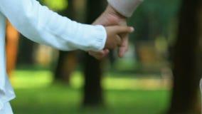 Ηλικιωμένη γυναίκα που παίρνει το χέρι του μικρού κοριτσιού και που περπατά στο πάρκο, οικογενειακό Σαββατοκύριακο, υπόλοιπο απόθεμα βίντεο