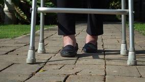 Ηλικιωμένη γυναίκα που πρήζεται πόδια που χρησιμοποιούν τον περιπατητή απόθεμα βίντεο