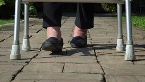 Ηλικιωμένη γυναίκα που πρήζεται πόδια που χρησιμοποιούν τον περιπατητή φιλμ μικρού μήκους