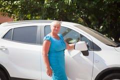 Ηλικιωμένη γυναίκα που στέκεται κοντά στο αυτοκίνητο στοκ φωτογραφίες