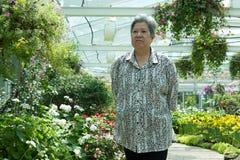 Ηλικιωμένη γυναίκα που στηρίζεται στον κήπο ηλικιωμένη θηλυκή χαλάρωση στο πάρκο Στοκ Φωτογραφία