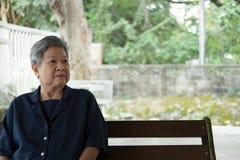 Ηλικιωμένη γυναίκα που στηρίζεται στον κήπο ηλικιωμένη θηλυκή χαλάρωση στο πάρκο Στοκ Φωτογραφίες