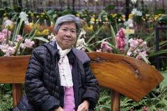 Ηλικιωμένη γυναίκα που στηρίζεται στον κήπο ηλικιωμένη θηλυκή χαλάρωση στο πάρκο Στοκ φωτογραφία με δικαίωμα ελεύθερης χρήσης