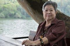 Ηλικιωμένη γυναίκα που στηρίζεται στον κήπο ηλικιωμένη θηλυκή χαλάρωση στο πάρκο Στοκ Εικόνα
