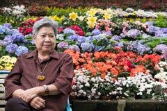 Ηλικιωμένη γυναίκα που στηρίζεται στον κήπο ηλικιωμένη θηλυκή χαλάρωση στο πάρκο Στοκ φωτογραφίες με δικαίωμα ελεύθερης χρήσης