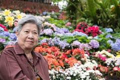 Ηλικιωμένη γυναίκα που στηρίζεται στον κήπο ηλικιωμένη θηλυκή χαλάρωση στο πάρκο Στοκ εικόνες με δικαίωμα ελεύθερης χρήσης