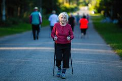 Ηλικιωμένη γυναίκα που συμμετέχεται στο σκανδιναβικό περπάτημα με τα ραβδιά αθλητισμός στοκ εικόνα
