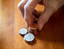 Ηλικιωμένη γυναίκα που συσσωρεύει τα νομίσματα σε έναν ξύλινο πίνακα στοκ φωτογραφία με δικαίωμα ελεύθερης χρήσης