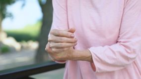 Ηλικιωμένη γυναίκα που τεντώνει το ναρκωμένο βραχίονα, αδυναμία των μυών στην ανώτερη ηλικία, αρθρίτιδα απόθεμα βίντεο