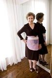 Ηλικιωμένη γυναίκα που φορά την ποδιά στοκ εικόνα