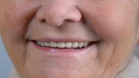 Ηλικιωμένη γυναίκα που χαμογελά στη κάμερα με τα καλά υγιή δόντια, την οδοντιατρική και τη στοματική φροντίδα φιλμ μικρού μήκους