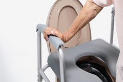 Ηλικιωμένη γυναίκα που χρησιμοποιεί την κινητή καρέκλα καθισμάτων τουαλετών στοκ εικόνα