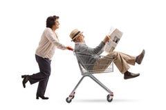 Ηλικιωμένη γυναίκα που ωθεί ένα κάρρο αγορών με έναν ώριμο άνδρα που οδηγά το ι Στοκ Εικόνες