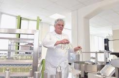 Ηλικιωμένη γυναίκα σε ένα εργοστάσιο για την παραγωγή της ιατρικής - ο καθ. στοκ εικόνα