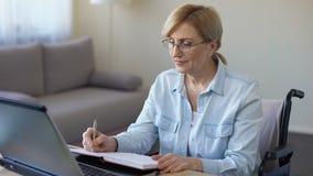 Ηλικιωμένη γυναίκα στην αναπηρική καρέκλα που έχει το σε απευθείας σύνδεση μάθημα με το δάσκαλο ΤΠ, που κάνει τις σημειώσεις απόθεμα βίντεο