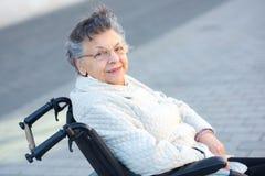 Ηλικιωμένη γυναίκα στην αναπηρική καρέκλα τοποθέτηση Στοκ Εικόνα