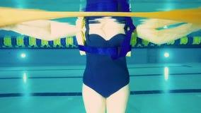 Ηλικιωμένη γυναίκα στις στάσεις γιλέκων στην πισίνα - υποβρύχιος πυροβολισμός απόθεμα βίντεο