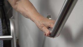 Ηλικιωμένη εκμετάλλευση γυναικών στο κιγκλίδωμα για τον περίπατο ασφάλειας απόθεμα βίντεο