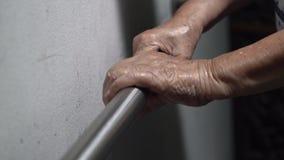 Ηλικιωμένη εκμετάλλευση χεριών γυναικών στο κιγκλίδωμα για την υποστήριξη φιλμ μικρού μήκους