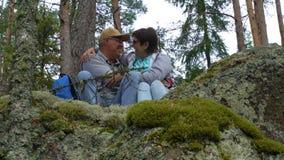 Ηλικιωμένη ενεργός συνεδρίαση ζευγών σε έναν βράχο και θαυμασμός του βόρειου δάσους φιλμ μικρού μήκους