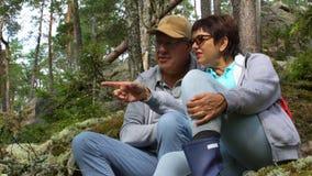 Ηλικιωμένη ενεργός συνεδρίαση ζευγών σε έναν βράχο και θαυμασμός του βόρειου δάσους απόθεμα βίντεο
