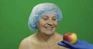 Ηλικιωμένη θηλυκή κυρία στο προστατευτικό καπέλο Ο γιατρός της παρουσιάζει ένα μήλο στοκ εικόνες με δικαίωμα ελεύθερης χρήσης