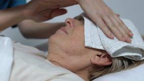Ηλικιωμένη κυρία που βρίσκεται στο κρεβάτι που πάσχει από τον πυρετό, νοσοκόμα που βάζει την υγρή πετσέτα στο μέτωπο απόθεμα βίντεο