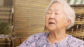Ηλικιωμένη κυρία που δείχνει τη κάμερα, καθισμένες ιστορίες αφήγησης, που έχει μια συνομιλία, εκφράσεις μιας ηλικιωμένης κυρίας απόθεμα βίντεο