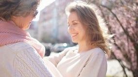 Ηλικιωμένη μητέρα που αγκαλιάζει την ενήλικη κόρη της που στέκεται στη μέση της οδού rogodskoy ενάντια στο σκηνικό φιλμ μικρού μήκους
