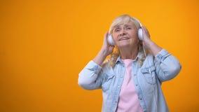 Ηλικιωμένη μουσική ακούσματος γυναικών στα ακουστικά, τον ελεύθερο χρόνο και την ψυχαγωγία απόθεμα βίντεο