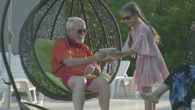 Ηλικιωμένη συνεδρίαση ζευγών σε μια χαλάρωση καρεκλών ένωσης στο ξενοδοχείο σύνθετο από κοινού Χαριτωμένο μικρό κορίτσι που στέκε απόθεμα βίντεο