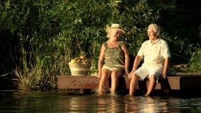 Ηλικιωμένη συνεδρίαση ζευγών στη λίμνη απόθεμα βίντεο