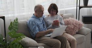 Ηλικιωμένη συνεδρίαση ζευγών στον καναπέ με το lap-top και τον καφέ φιλμ μικρού μήκους