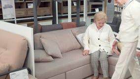 Ηλικιωμένοι σύζυγος και σύζυγος που δοκιμάζουν το νέο καναπέ, που ψωνίζει για τα έπιπλα απόθεμα βίντεο