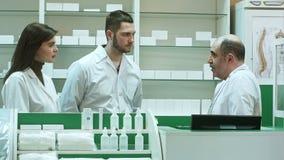 Ηλικιωμένοι φαρμακοποιός και βοηθοί που μιλούν σοβαρά στην υποδοχή farmacy απόθεμα βίντεο