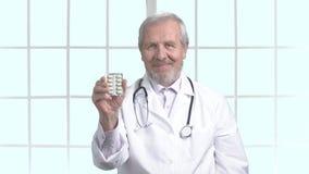 Ηλικιωμένος γιατρός που χαμογελά με τη φουσκάλα των χαπιών απόθεμα βίντεο