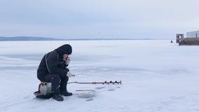 Ηλικιωμένος ψαράς στα σκοτεινά ενδύματα που αλιεύει στη ράβδο χειμερινής αλιείας στον παγωμένο ποταμό και το καυτό τσάι ή τον καφ απόθεμα βίντεο