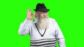 Ηλικιωμένο άτομο με τη γενειάδα που παρουσιάζει ΕΝΤΑΞΕΙ σημάδι φιλμ μικρού μήκους