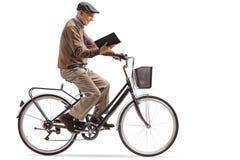 Ηλικιωμένο άτομο που οδηγά ένα ποδήλατο και που διαβάζει ένα βιβλίο Στοκ φωτογραφίες με δικαίωμα ελεύθερης χρήσης