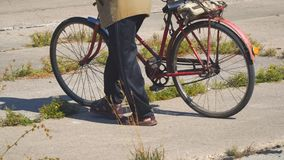 Ηλικιωμένο άτομο που περπατά κάτω από την οδό με το παλαιό ποδήλατο απόθεμα βίντεο