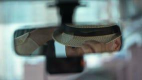 Ηλικιωμένο άτομο που φορά το καπέλο και που κοιτάζει στον οπισθοσκόπο καθρέφτη αυτοκινήτων, κινηματογράφηση σε πρώτο πλάνο οδηγών απόθεμα βίντεο