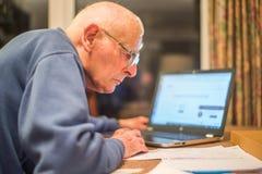 Ηλικιωμένο άτομο που χρησιμοποιεί έναν φορητό προσωπικό υπολογιστή για να ελέγξει τα χαρτοφυλάκια μεριδίου, Χάμπσαϊρ, Αγγλία, U ? στοκ φωτογραφία με δικαίωμα ελεύθερης χρήσης