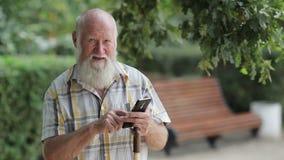 Ηλικιωμένο άτομο στη δακτυλογράφηση πάρκων στο κινητό τηλέφωνο απόθεμα βίντεο